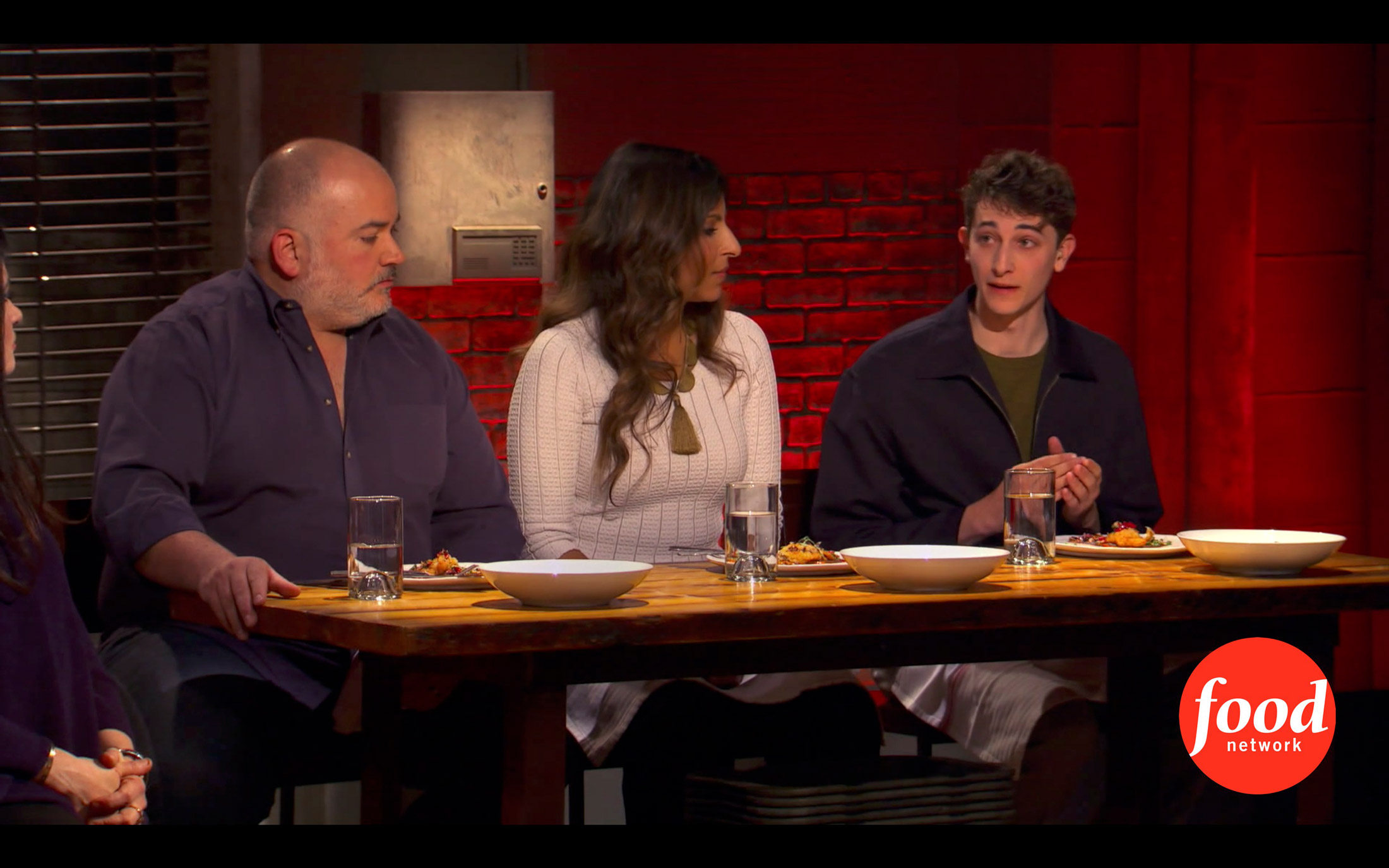 Jonah on a Food Network show, sitting alongside two others, each with a plate of food in front of them.