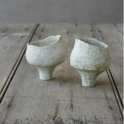 Two unconventional hand-shaped ceramic tea bowls on a wooden table